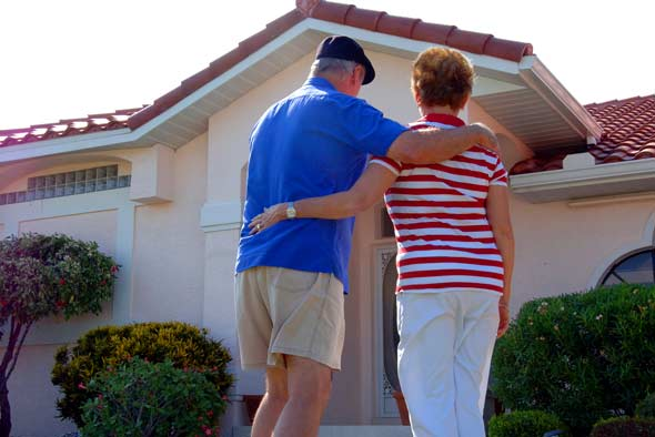 senior-couple-in-front-of-homejpg